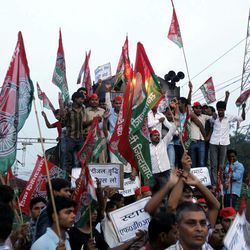 """Samajwadi Party activists hold party flags and block a railway track during a protest in Allahabad, India, Thursday, Sept. 20, 2012.  Angry opposition workers have disrupted train services as part of a daylong strike in India to protest rising diesel prices and the government's decision to open the country's huge retail market to foreign companies. Placards read """"Take Walmart back."""""""