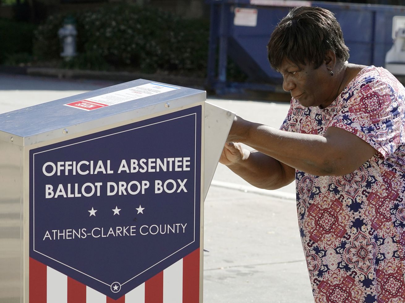 In this Oct. 19, 2020 file photo, a voter drops their ballot off during early voting in Athens, Ga. After record turnout led to stunning GOP losses in the once reliably red state, Republican lawmakers are forging ahead with an aggressive slate of voting legislation that critics argue is tailored toward curtailing the power of Black voters.