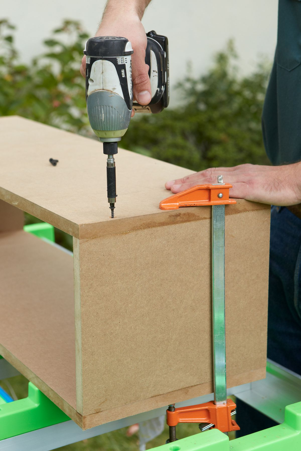Man Countersinking Pilot Holes In Wood To Make Room Divider