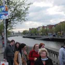 A government poster calling on voters to support Europe's fiscal treaty looms over pedestrians along the River Liffey in Dublin, Ireland, on Monday, April 30, 2012. Voters must decide May 31 whether to accept the European Union's tougher budget rules proposed in the treaty. Rejection could block Ireland from receiving further EU loans in 2013, a prospect that Ireland's government says must be avoided at all costs.