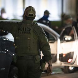 Officers with the U.S. Marshals Service Department keep watch as Kenosha police officers take a man into custody for violating the city's 7 p.m. curfew on the fifth night of unrest after police shot Jacob Blake, Thursday night, Aug. 27, 2020.