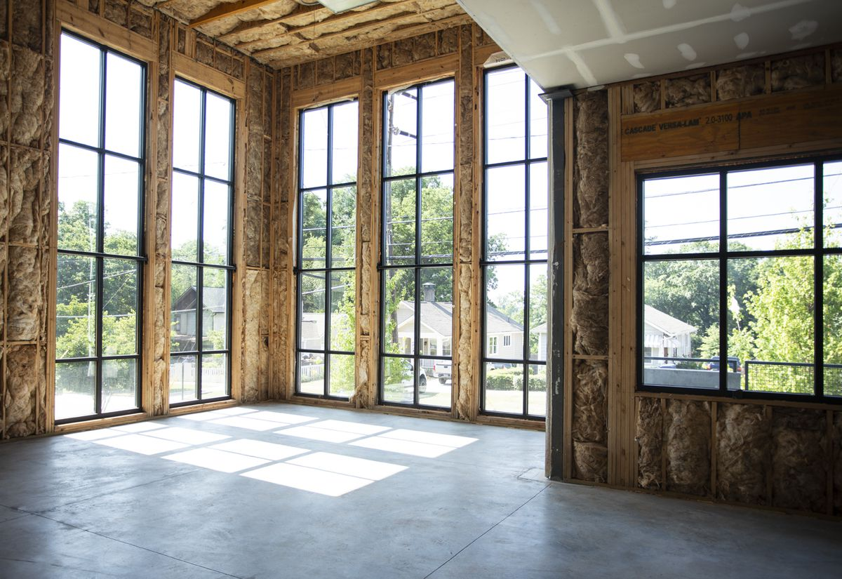 An unfinished look inside Purpose Built's new office space, which features lofted ceilings and tall windows.
