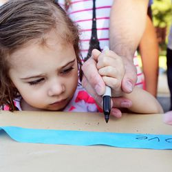 Audrey Friden gets some help from her dad, Christian Friden, writing a message on a ribbon as community members gather to tie ribbons and write messages to the Rackley family and first responders of the murder-suicide along Alta Canyon Drive in Sandy on Saturday, June 10, 2017.