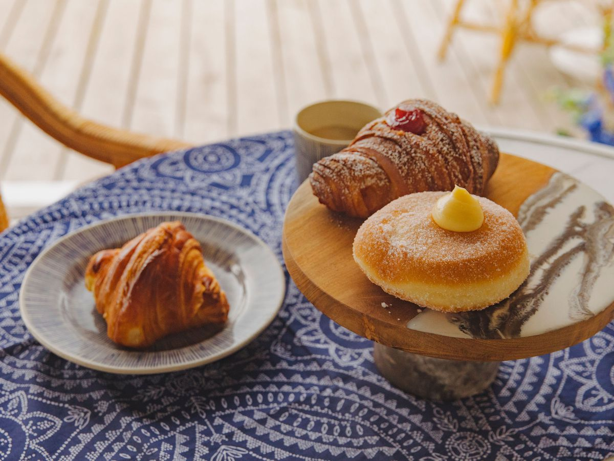 Croissants and filled cream doughnuts sit on a tray on an ornate blue and white patterned table