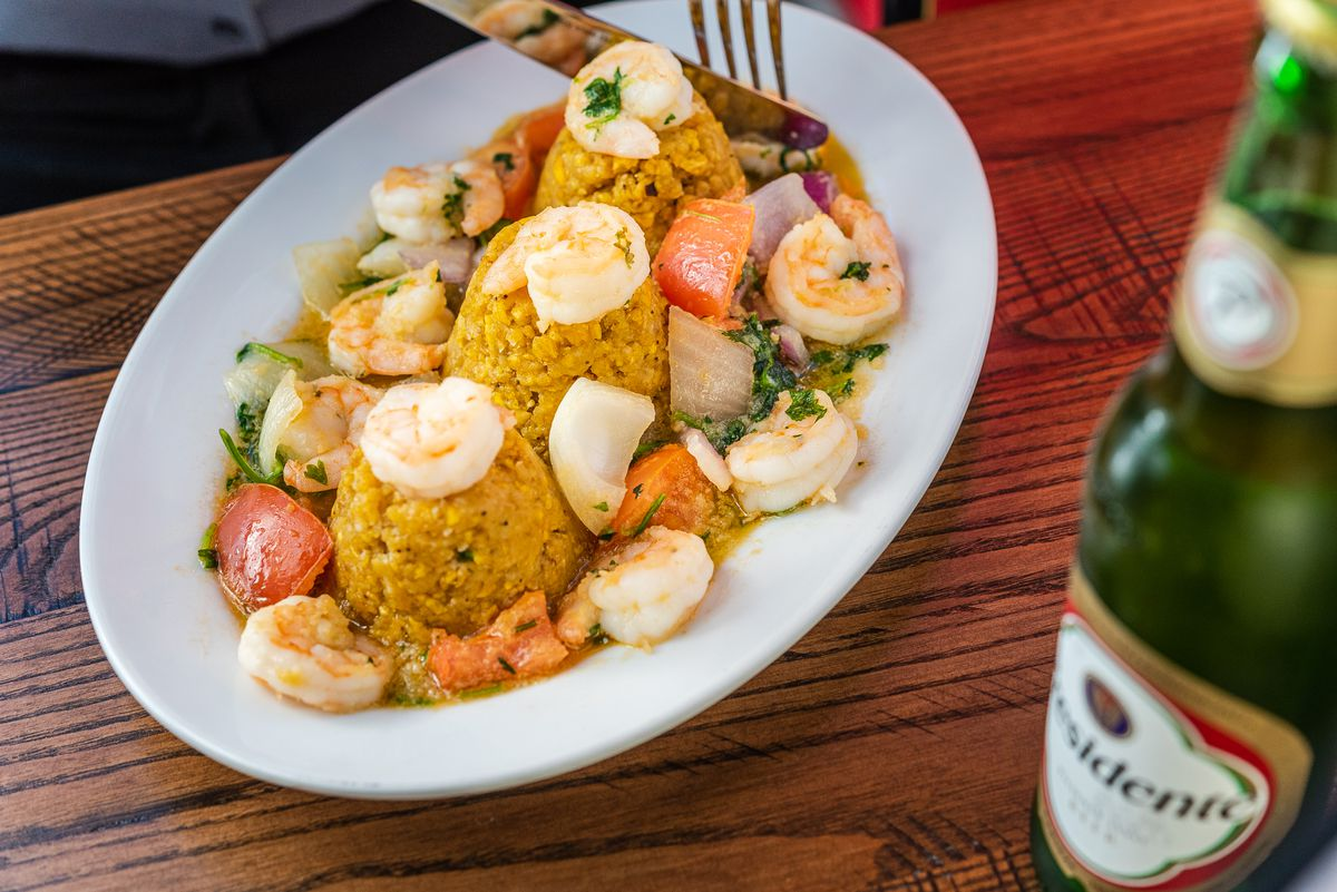 A plate of shrimp mofongo featuring three scoops of mashed plantains topped with seafood and vegetables