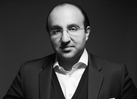 A black and white photo of Steven Kamali, who wears glasses and a suit.