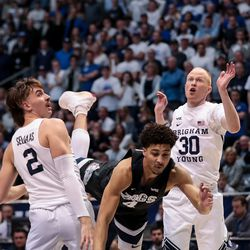 Gonzaga Bulldogs guard Ryan Woolridge (4) loses the ball as he drives between Brigham Young Cougars guard Zac Seljaas (2) and guard TJ Haws (30) at the Marriott Center in Provo on Saturday, Feb. 22, 2020.