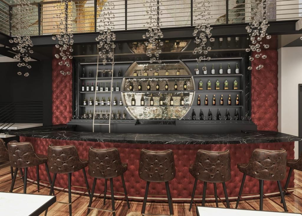 The bar at Steak Market in Atlanta with leather-backed stools, plush red velvet panelling along the back bar and under the bar top