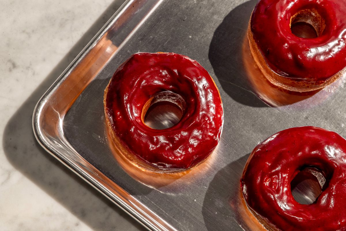 Three red rice doughnuts on a stainless steel tray