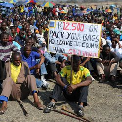 Striking Lonmin Platinum miners gather in Marikana, South Africa, where a new wage offer was rejected Friday, Sept. 14, 2012.   As various stakeholders continued negotiations Justice Minister Jeff Radebe warned that the Government would clamp down on daily illegal marches by miners brandishing machetes, spears and clubs that have marked the strike. (AP Photo)