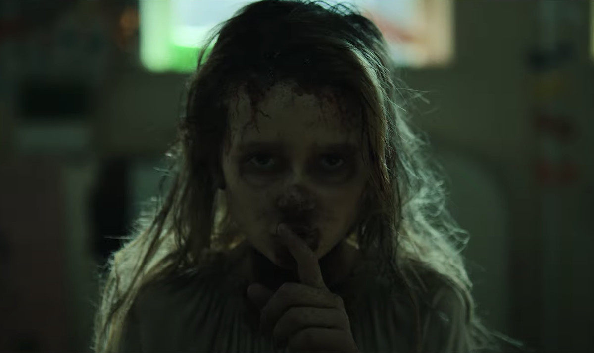 a close up shot of a young girl with dirty wearing a mask of human flesh shushing with her left index finger