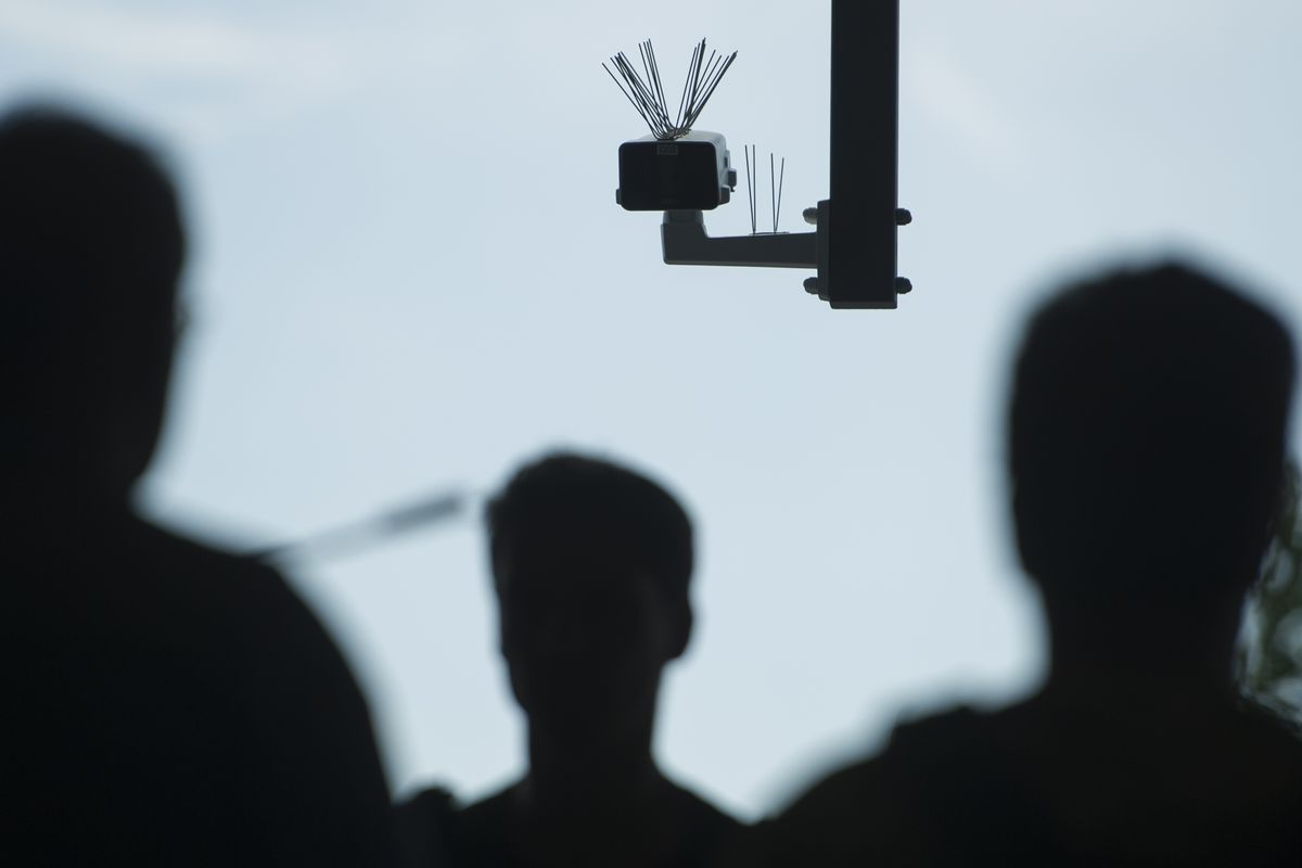 A surveillance camera in Germany, with the silhouettes of several passersby in the foreground.