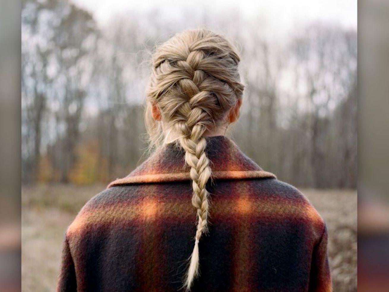 Swift se tient dos à la caméra, les cheveux dans une tresse française