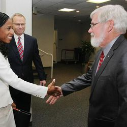 Mia Love and Doug Owens are greeted by University of Utah President David W. Pershing on Tuesday, Oct. 14, 2014, prior to their debate in the KUED studios in Salt Lake City.