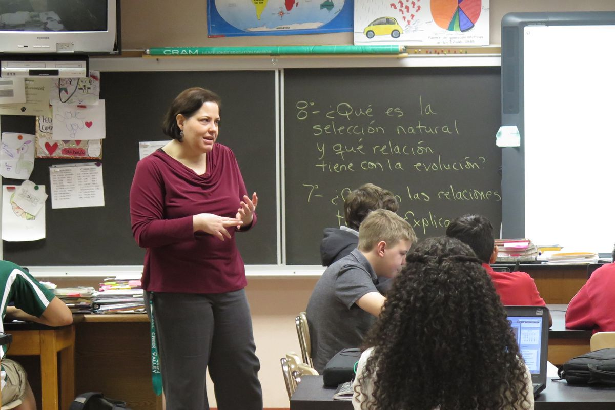 A woman in a maroon blouse instructs her class, standing in between the desks of her students