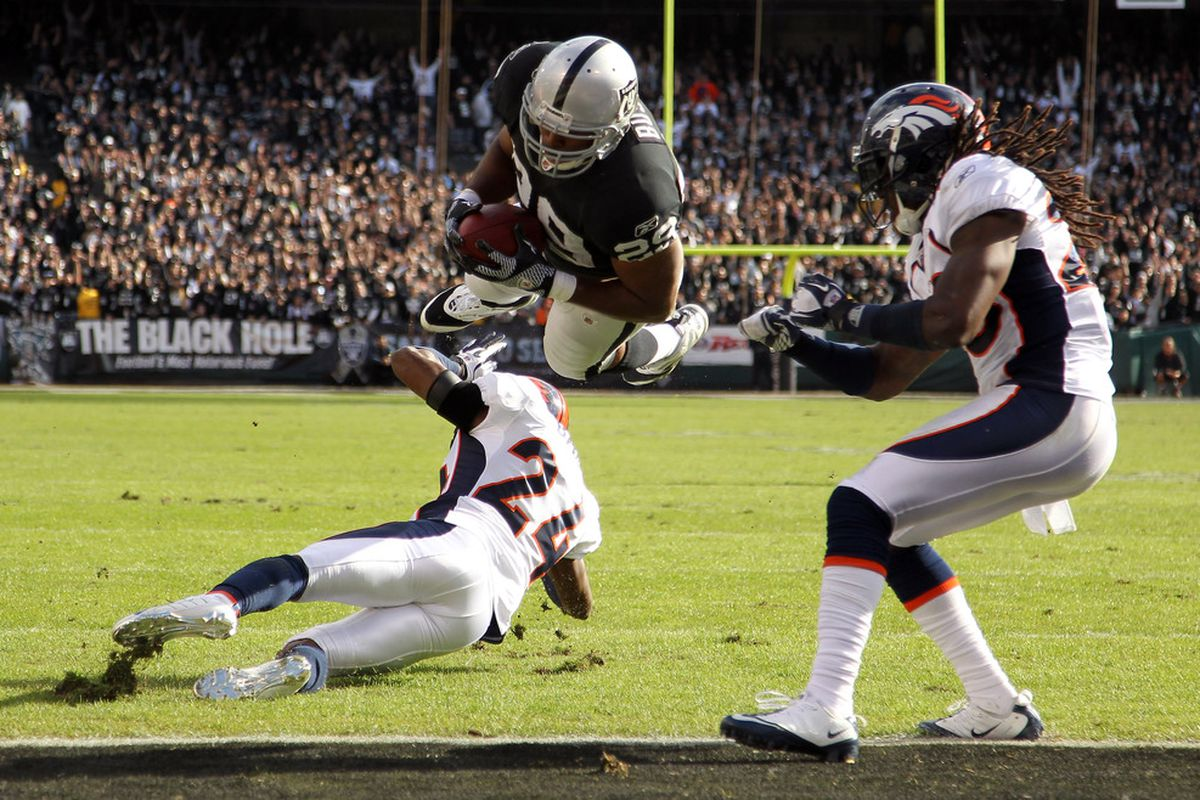 OAKLAND, CA - NOVEMBER 06:  Michael Bush #29 of the Oakland Raiders dives over Champ Bailey #24 of the Denver Broncos to score a touchdown at O.co Coliseum on November 6, 2011 in Oakland, California.  (Photo by Ezra Shaw/Getty Images)