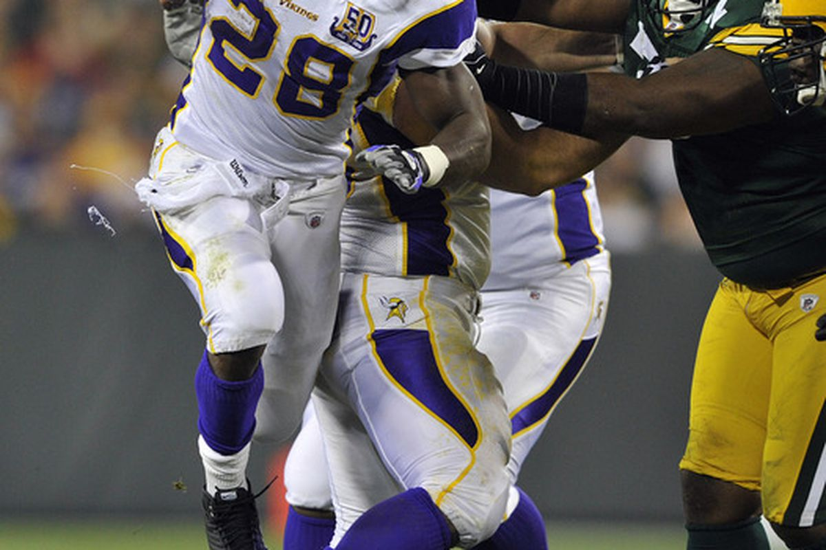 GREEN BAY WI - OCTOBER 24:  Adrian Peterson #28 of the Minnesota Vikings leaps in the air for extra yardage against the Green Bay Packers at Lambeau Field on October 24 2010 in Green Bay Wisconsin. (Photo by Jim Prisching/Getty Images)