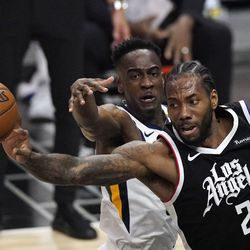 Los Angeles Clippers forward Kawhi Leonard, right, passes the ball while under pressure from Utah Jazz guard Miye Oni during the second half of Game 3 of a second-round NBA basketball playoff series Saturday, June 12, 2021, in Los Angeles.
