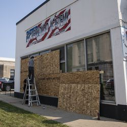 Business owners board up windows in downtown Kenosha in the wake of unrest overnight after police shot a Black man, Jacob Blake, in the the 2800 block of 40th Street, Monday morning, Aug. 24, 2020.