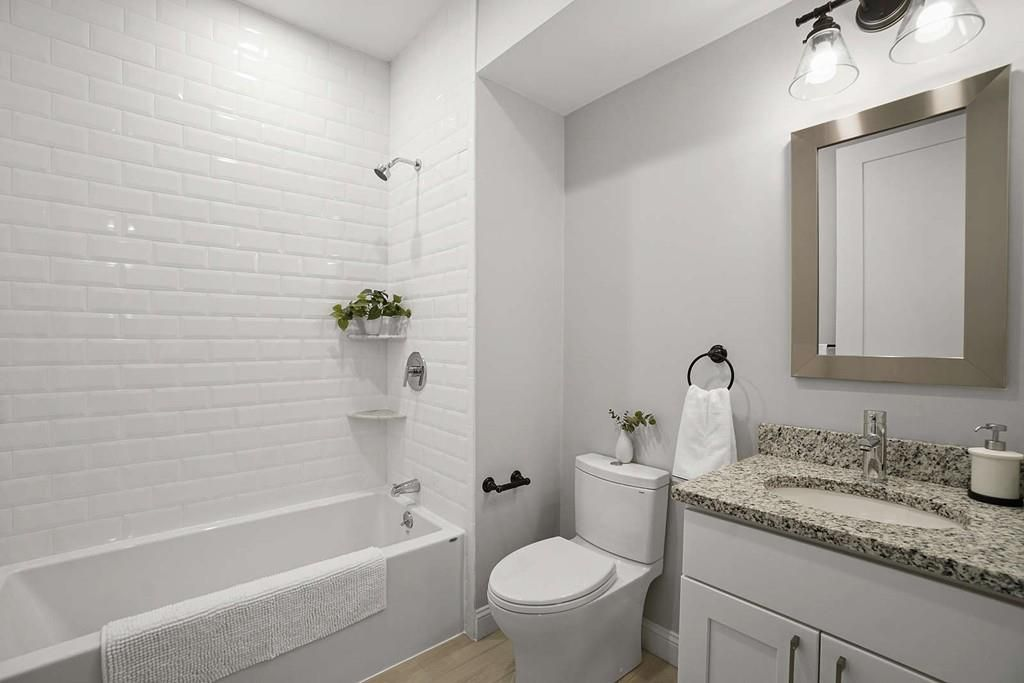 A bathroom with no shower curtain on the tub.
