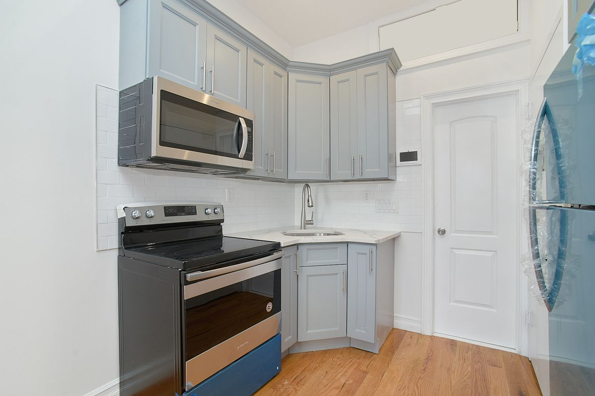 A small kitchen with light blue cabinetry.