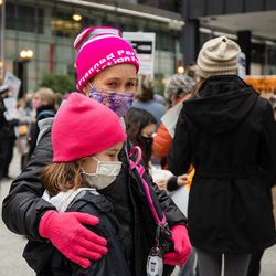A mother and her daughter attend the Women's March at Federal Plaza in the Loop Saturday morning.