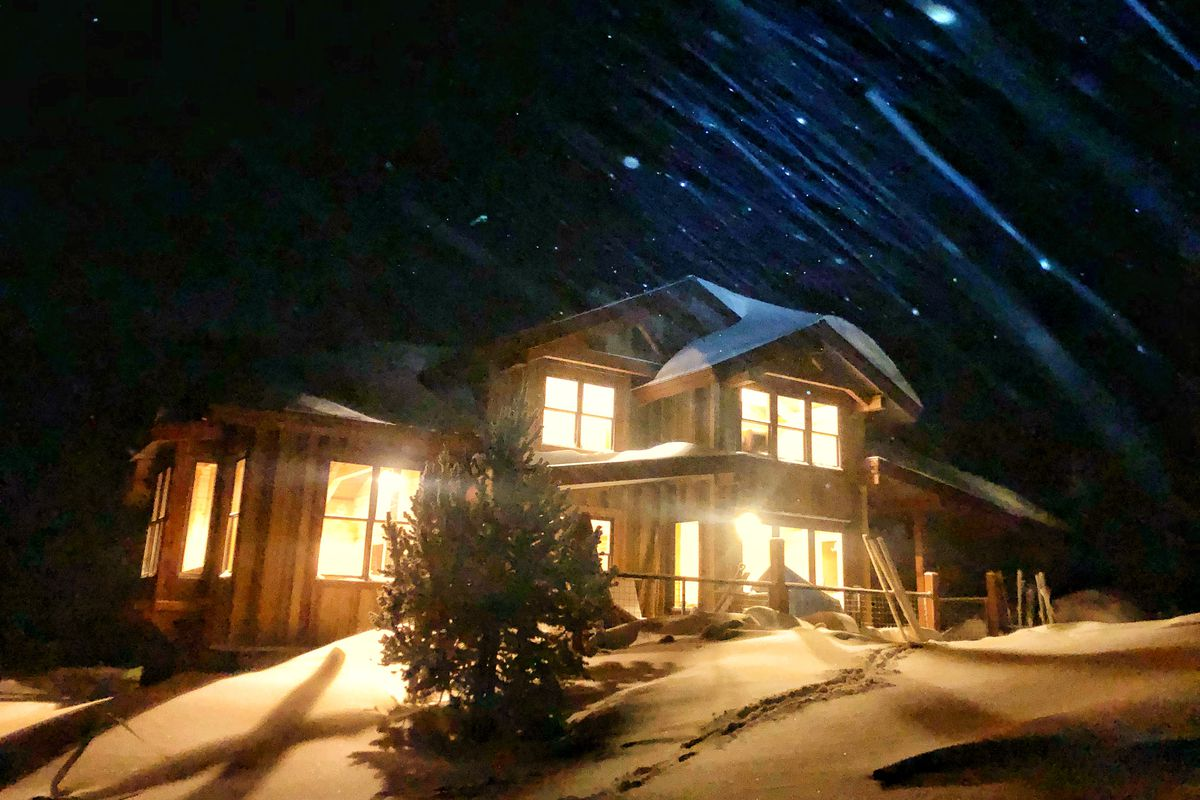A wooden house lit up at night with glowing windows, stars above, and snow all around the exterior.