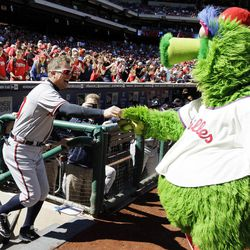 Atlanta Braves' Chipper Jones, left, laughs as he returns keys to the Philadelphia Phillies mascot, the Phillie Phanatic, after Jones stole them from the Phanatic's all-terrain vehicle before a baseball game between the Phillies and Braves, Sunday, Sept. 23, 2012, in Philadelphia.