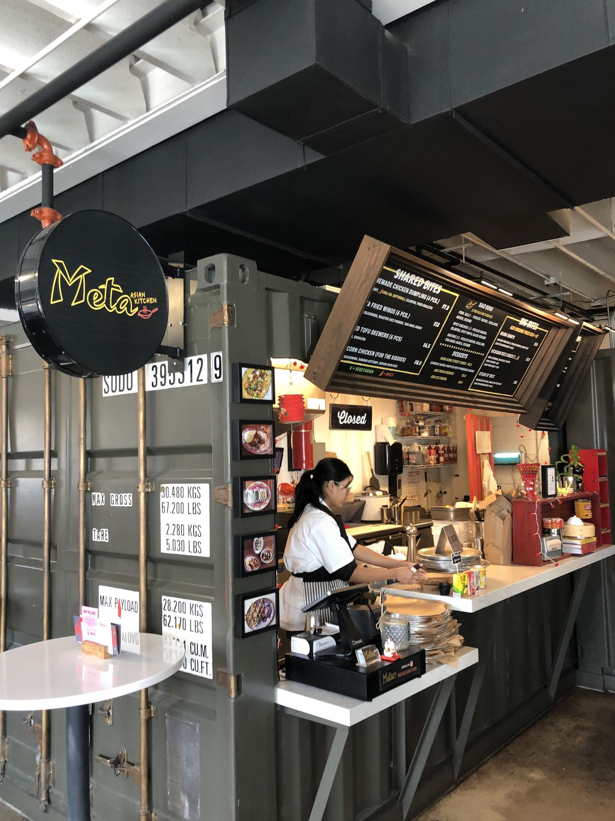 A photo of Meta Asian Kitchen, which is set in a metal shipping container at Avanti Food & Beverage, with a round sign and the menu visible