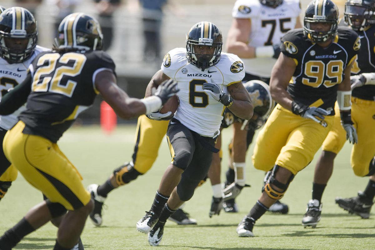 Missouri running back Marcus Murphy, center, splits defenders George White (99) and Robert Steeps (22) during the first half of an NCAA college football scrimmage  game Saturday, April 14, 2012, in Columbia, Mo.