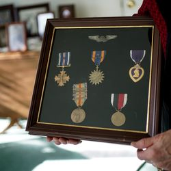 Helen Lower Simmons holds medals awarded to her brother, Max Wendell Lower, during World War II, top four, and her father, Samuel Steven Lower, during World War I, bottom two, at her home in Logan on Thursday, Nov. 14, 2019. Max Lower was killed when his plane was shot down during the Operation Tidal Wave attacks on Romanian oil refineries during the war. His remains were recently identified using DNA technology and will soon be returned to his family in Utah.