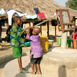 Children in an African village pump water from a well installed with help from the LDS Church in 2015.