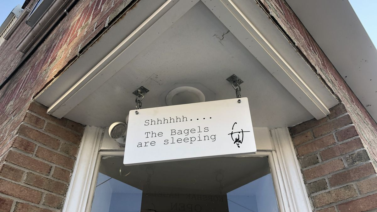 the front entrance of korshak bagels with a sign hanging that says shh...the bagels are sleeping