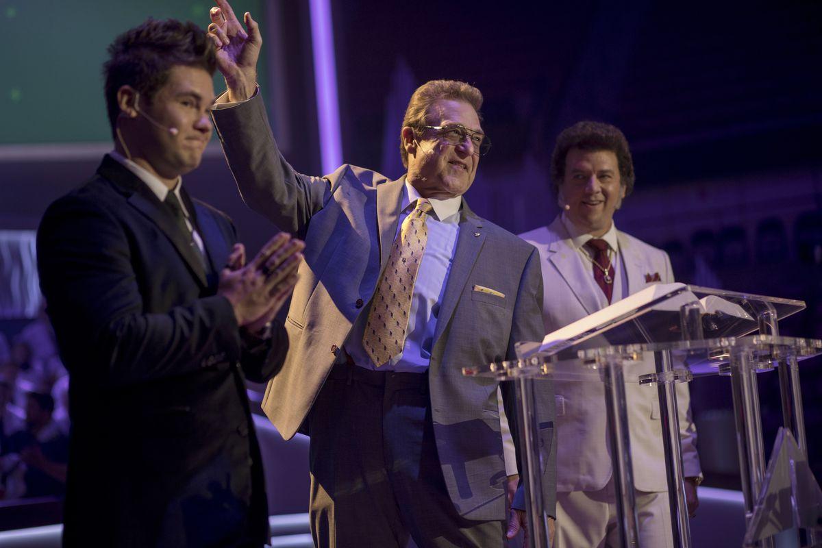 Kelvin (Adam Devine), Eli (John Goodman), and Jesse (McBride) stand behind a podium in The Righteous Gemstones