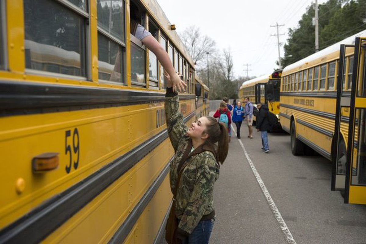 In a 2015 photo, a student says goodbye to her friend as the pair board buses for home at the end of a school day at Bartlett Ninth Grade Academy.