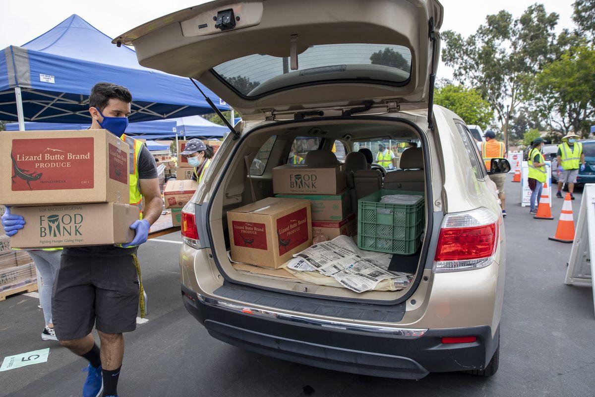 Volunteer loads food into a car for LA Regional Food Bank.