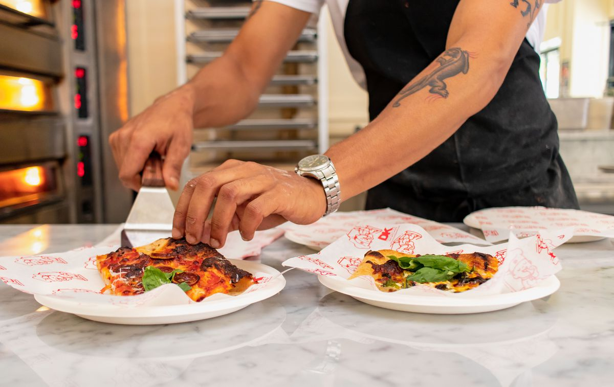 A tattooed arm places a square slice of pizza on a paper plate