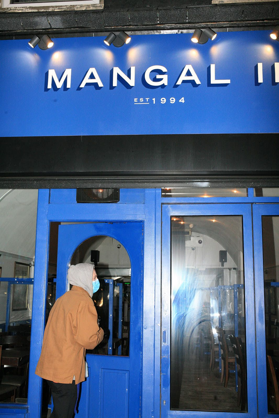 A customer in a mask enters Mangal 2 on the day it reopened after the second coronavirus lockdown in London, December 2020