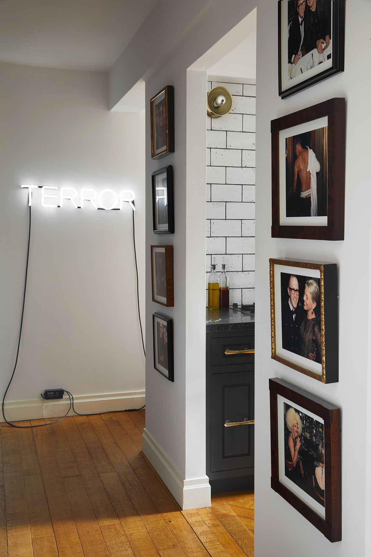A hallway has a neon sign and many pictures from the designer's 50th birthday party.