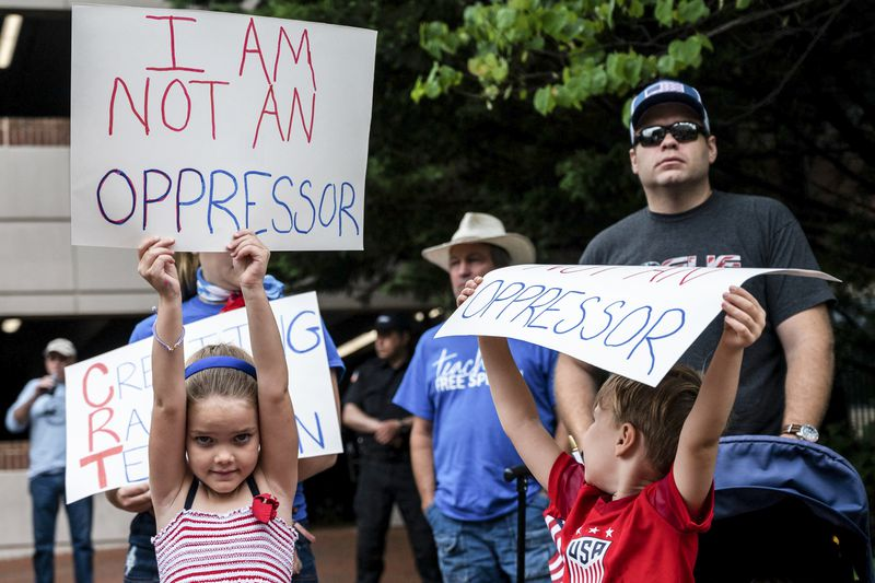 """Young children at a rally hold signs that read """"I am not an oppressor."""""""