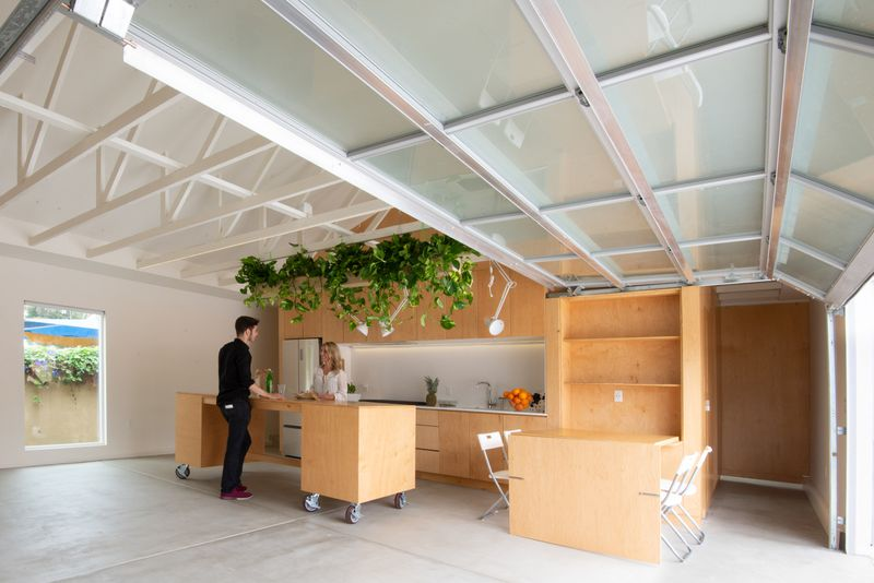 Kitchen in an open space made of plywood and featuring a pull-down table and movable island.