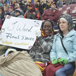 A member of Jonathan Ward's family holds up a sign and cheers during the first quarter of action.