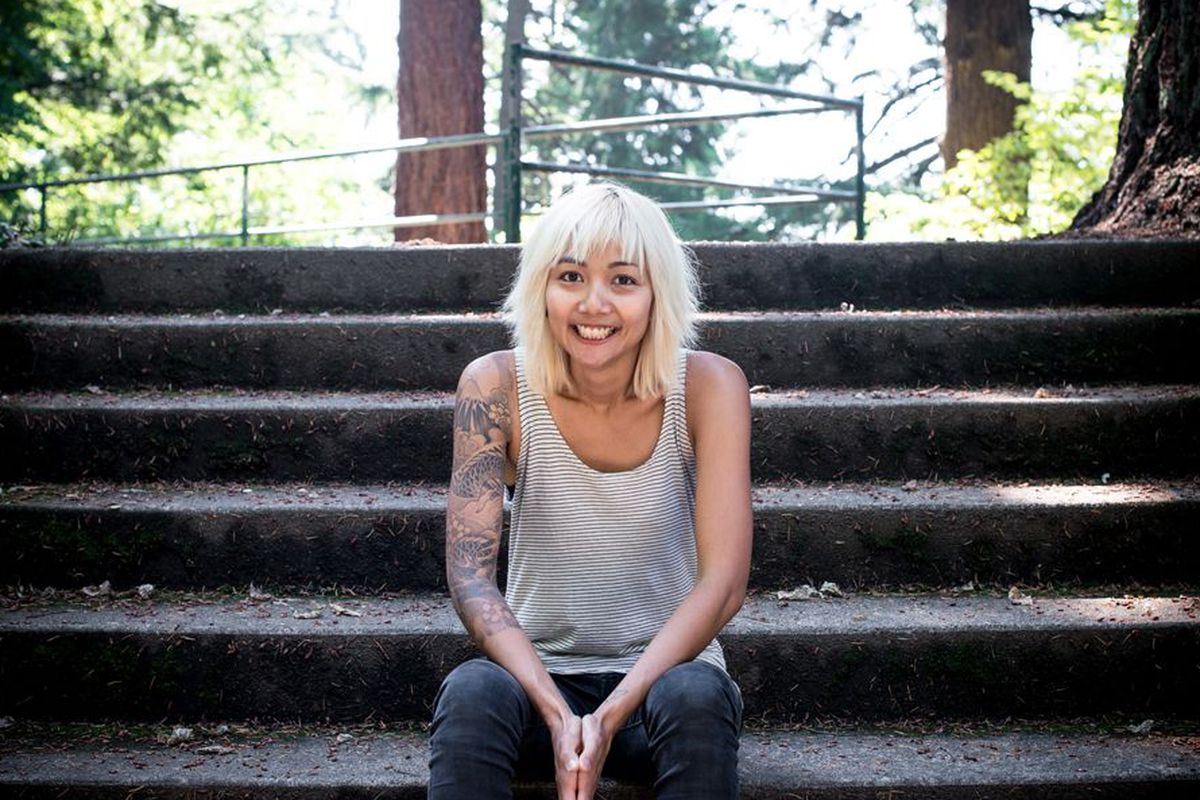 Nong Poonsukwattana — a woman with tattoos and shaggy, white hair — sits on the steps of a Portland park.