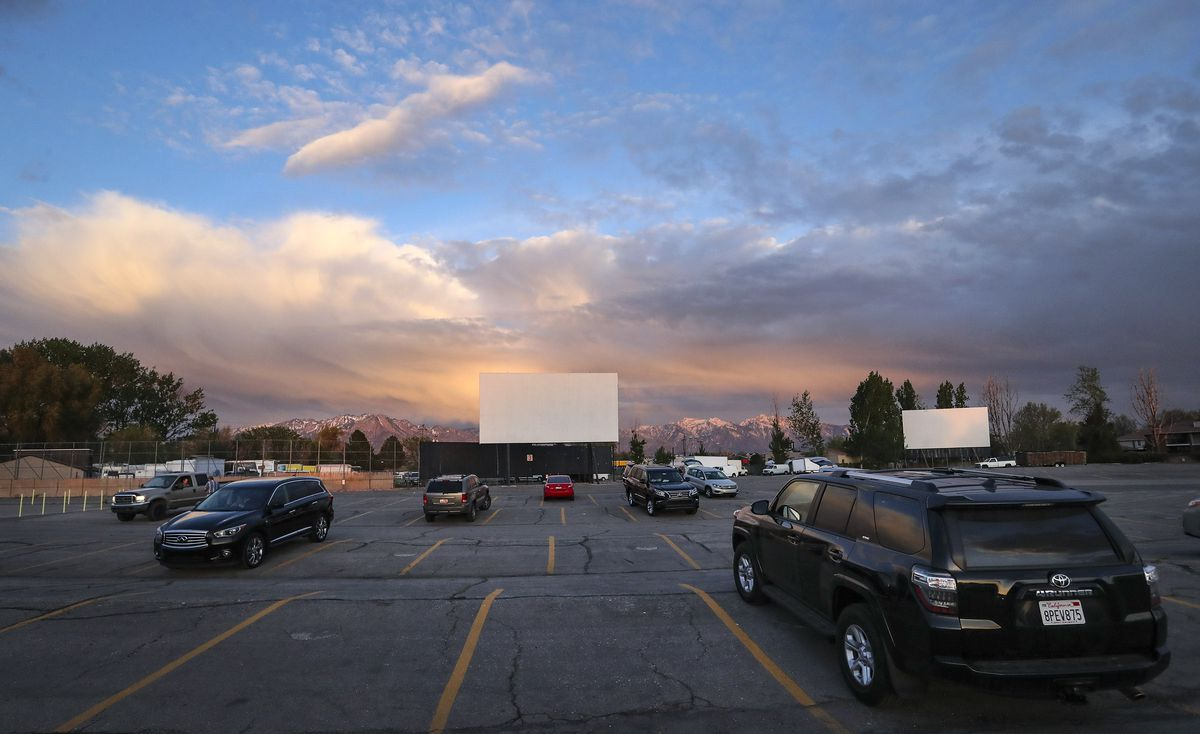 Moviegoers park their cars with at least two open spaces between each vehicle at the Redwood Drive-In Theatre in West Valley City on Friday, May 1, 2020. The drive-in was closed because of the COVID-19 pandemic but has recently reopened.