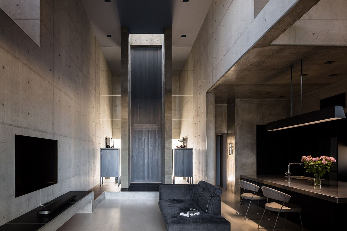 The living area in a concrete house. The ceilings are high, there is a couch, chairs, kitchen island, and a window.