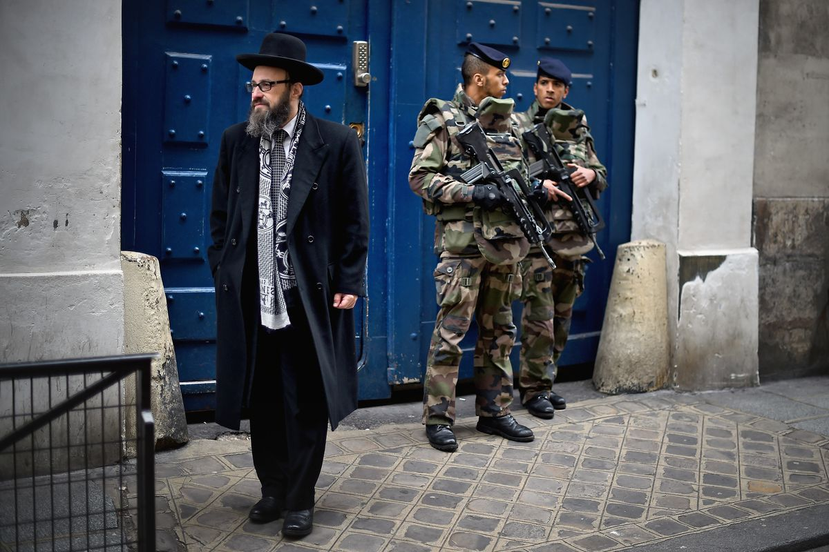 Armed soldiers patrol outside a School in the Jewish quarter of the Marais district on January 13, 2015 in Paris, France.