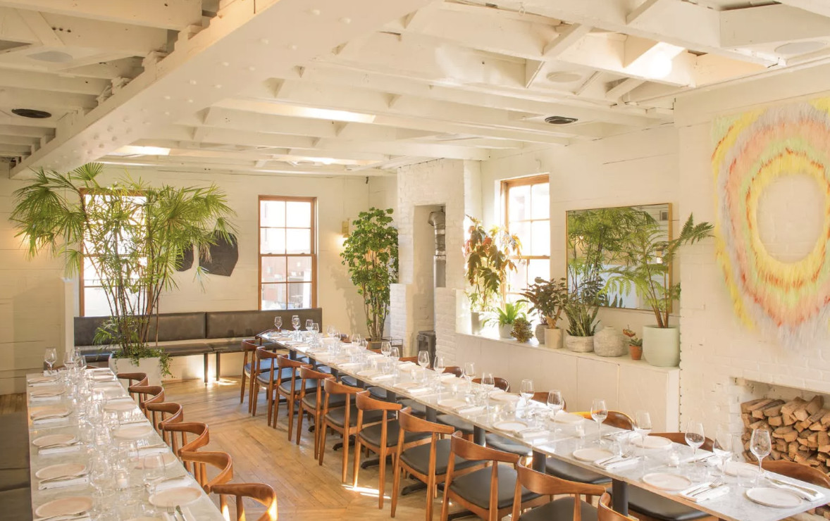 A light and bright room decorated with plants and set with two long tables