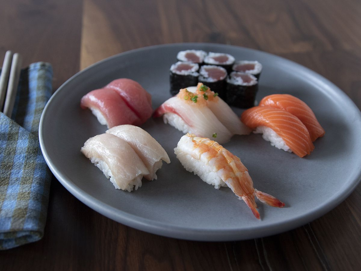 A plate of several pairs of fish and shrimp nigiri, and a maki roll