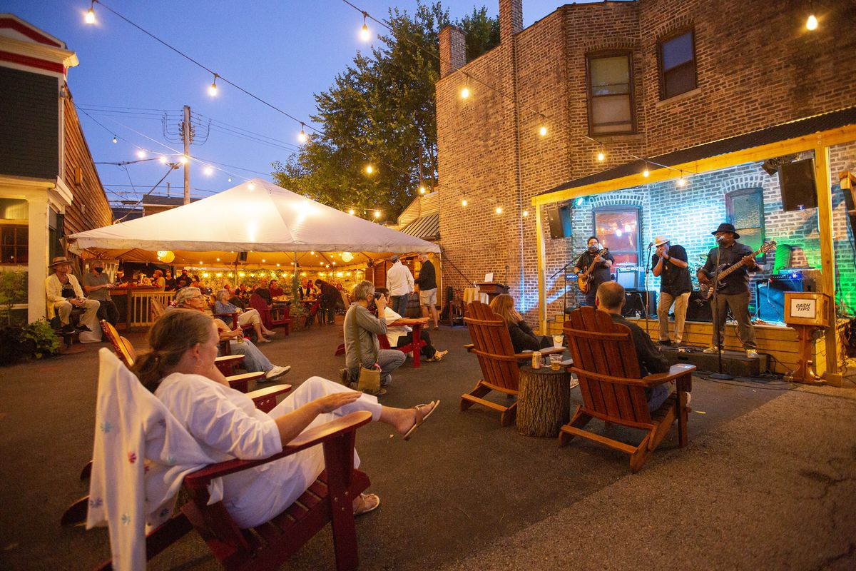 A nighttime scene in a patio with people sitting and watching live music.