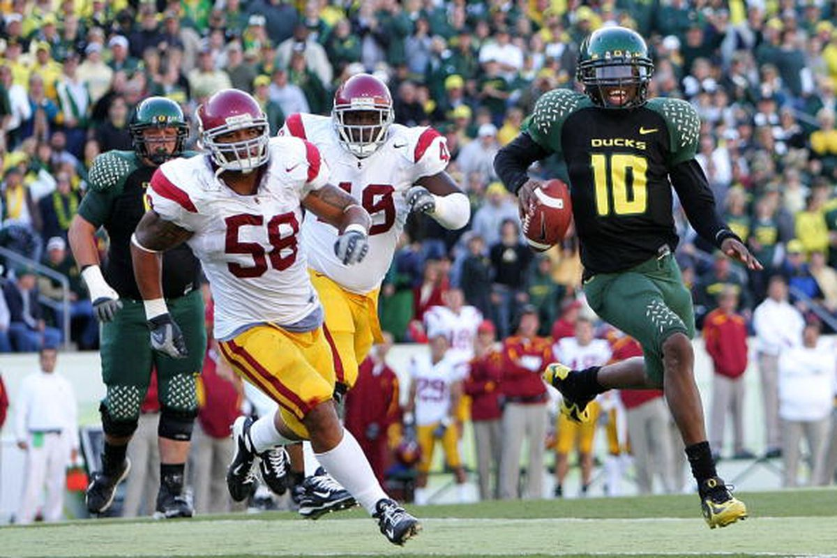 EUGENE, OR - OCTOBER 27: Quarterback Dennis Dixon #10 of the Oregon Ducks runs with the ball against Ryan Maualuga #58 of the Southern California Trojans at Autzen Stadium October 27, 2007 in Eugene, Oregon. (Photo by Jonathan Ferrey/Getty Images)